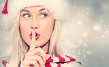 Woman with Santa hat making quiet gesture