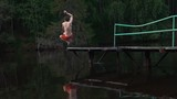 Young man jump into water of lake with go pro camera in hands. Summer. Flips. Emotions. Slow motion