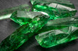 Closeup of a bunch of many green rough uncut emerald crystals