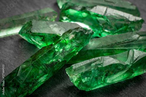 Closeup of a bunch of many green rough uncut emerald crystals