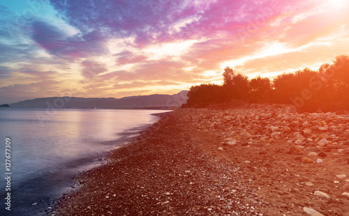 Poster Oranje eclat Beautiful colorful sunrise at the sea with dramatic clouds and seashore with boulders