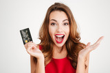 Happy excited amazed young woman holding credit card - 127678141