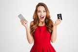 Cheerful excited young woman with mobile phone and credit card