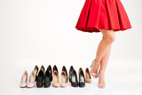 Woman in red dress standing near pairs of shoes
