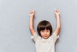 Portrait of happy little boy pointing up with both hands