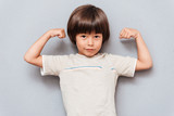Cute little boy standing and showing biceps