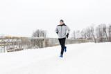 man running along snow covered winter bridge road