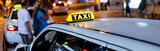 Taxi sign on the roof of a taxi at night - 127692727