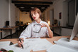 Woman fashion designer drawing sketches at the table in office