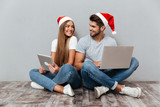 Christmas photo of couple with laptops