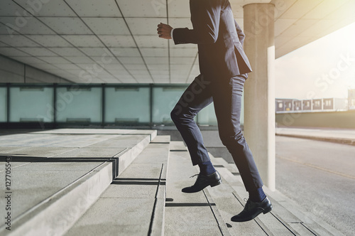 Man wearing suit runs up the stairs