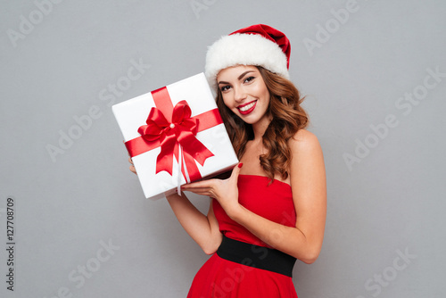 Woman in santa's hat and dress holding a box