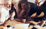 Closeup concept of business people brainstorming.Bearded man talking with account director and creative manager to finding great work solution.Horizontal, blurred background.