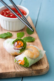 Vietnamese rolls with vegetables, rice noodles and prawns on blue wooden background