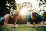 Caucasian couple doing core workout in park