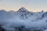 Dramatic mountain view of Ama Dablam summit on the famous Everest Base Camp trek in Himalayas, Nepal. Beautiful landscape with white clouds in front of the mountain peak lit up by the first sun light.