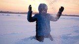 g child throwing snow over himself and enjoys it in winter park at sunset