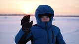 child waving hand greeting in winter park at sunset