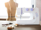 Tailor workshop with white sewing machine, fashion dummy, detail