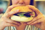 Woman hands holding a hamburger.