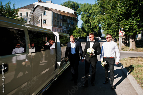 Three handsome guys walking into luxury limousine. Groom with be Poster