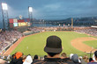 Baseball fan watching night game in San Francisco. The fan is wearing a black baseball cap turned backwards and a black jacket with orange piping. We can see the infield, outfield, stadium lights.