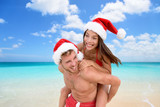 Christmas vacation beach couple doing piggyback fun. paradise beach travel holidays Asian bikini woman having fun man carrying girl laughing in christmas santa hat.