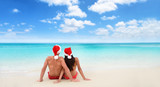 Christmas beach vacation holidays santa hat couple relaxing from behind sitting on white sand wide horizontal sky background for text advert for holiday season. Blue ocean texture.