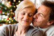 Senior couple in front of Christmas tree kissing, close up.