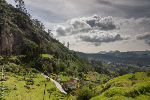 Foto Murales Ooty, India - October 25, 2013: Panoramic scenery of the Nilgiri hills shows forest, many hills at horizon, free floating stormy clouds, rocks, a road and a farm. Shades of green. Shot from us a hill.