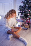 young pretty woman smiles and lying on carpet with a pen writing a christmas letter