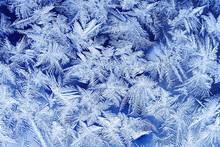 Bellissimo modello gelido di festa con i fiocchi di neve bianca su sfondo blu su vetro