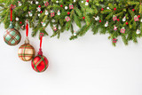 Christmas background. Christmas fir tree branch with decoration on white wooden board background. Top view, copy space.