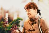 Senior woman buying Christmas decoration.
