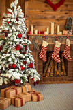 Fototapety Beautiful holiday decorated home room with Christmas tree, gifts under it and red Christmas socks.
