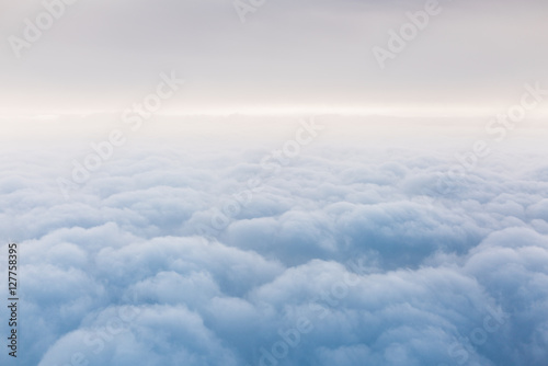 Above the clouds. A view from an airplane. - 127758395