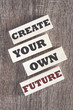 Create your own future. Motivational quote written on wooden tiles