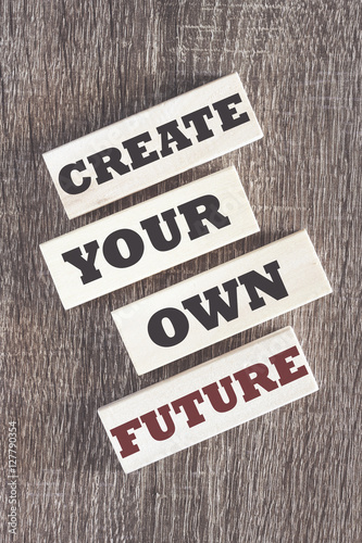 Create your own future. Motivational quote written on wooden tiles Photo by yiorgosgr