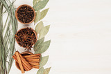 Spices - aniseed, cinnamon, cloves and herbs in wooden bowls on a wood white background. Spicy seasonings for cooking. Top view.