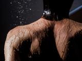 Donna sotto la doccia con sfondo nero