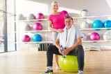 Fototapety Senior couple exercising in gym