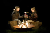 children sitting beside the campfire with marshmallow and chocolate