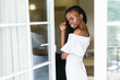 beautiful African girl standing in front of the open door. body is reflected in the glass. girl wearing white dress.