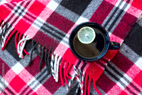 Poster Black cup with tea and lemon standing on warm red checkered plaid
