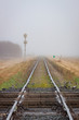 Two Railroads Crossing With Track Receding into Fog