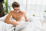 Cheerful guy entertaining with computer in bedroom