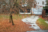 panel path next to fallen tree  leading to metal gates during autumnal rainy weather  in Chomutov city in czech republic