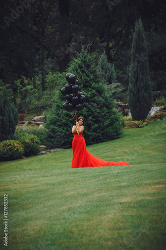 Poster Gorgeous woman in red dress with black balloons