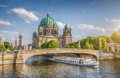 Leinwanddruck Bild Berlin Cathedral with ship on Spree river at sunset, Berlin Mitte, Germany