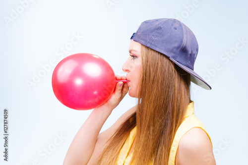 Poster Female teenager inflating red balloon.